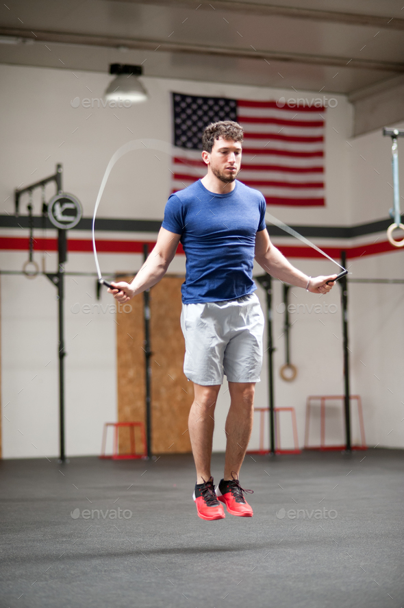 Fit athletic young man using a skipping rope - Stock Photo - Images