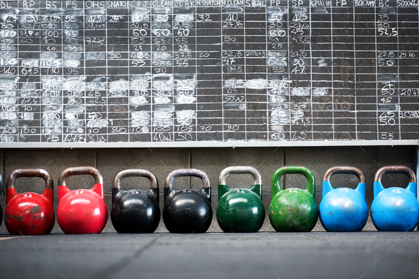 Row of colorful pairs of kettlebell weights - Stock Photo - Images