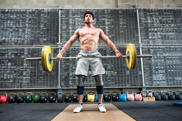 Strong man lifting heavy barbell - Stock Photo - Images