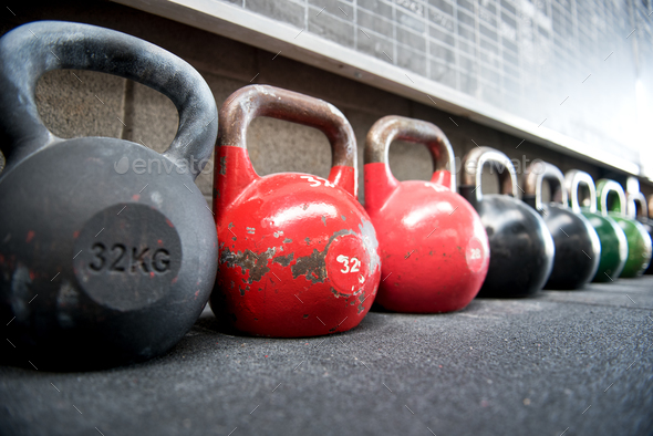 Long receding row of kettlebell weights in a gym - Stock Photo - Images