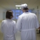Back View of Male and Female Doctors Dressed in Lab Coats Walking Through the Corridor of the Ward - VideoHive Item for Sale