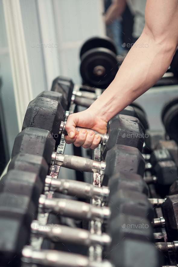 Powerlifter is picking a dumbbell - Stock Photo - Images