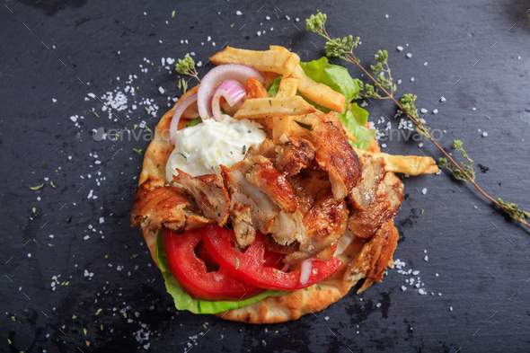 Greek gyros dish on a black dish - top view - Stock Photo - Images