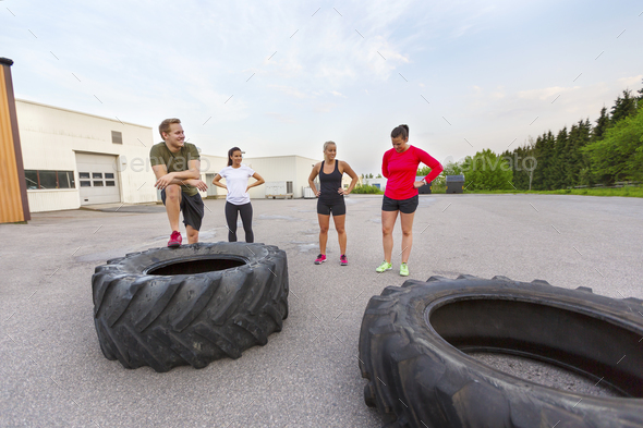 Workout team taking a break from flipping tire training outdoor - Stock Photo - Images