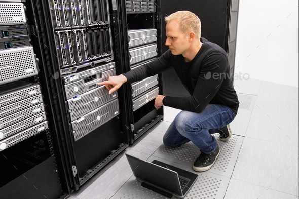 It consultant work with laptop in datacenter - Stock Photo - Images