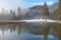 foggy winter morning by lake in mountains