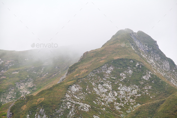 mountain peak in dense fog - Stock Photo - Images