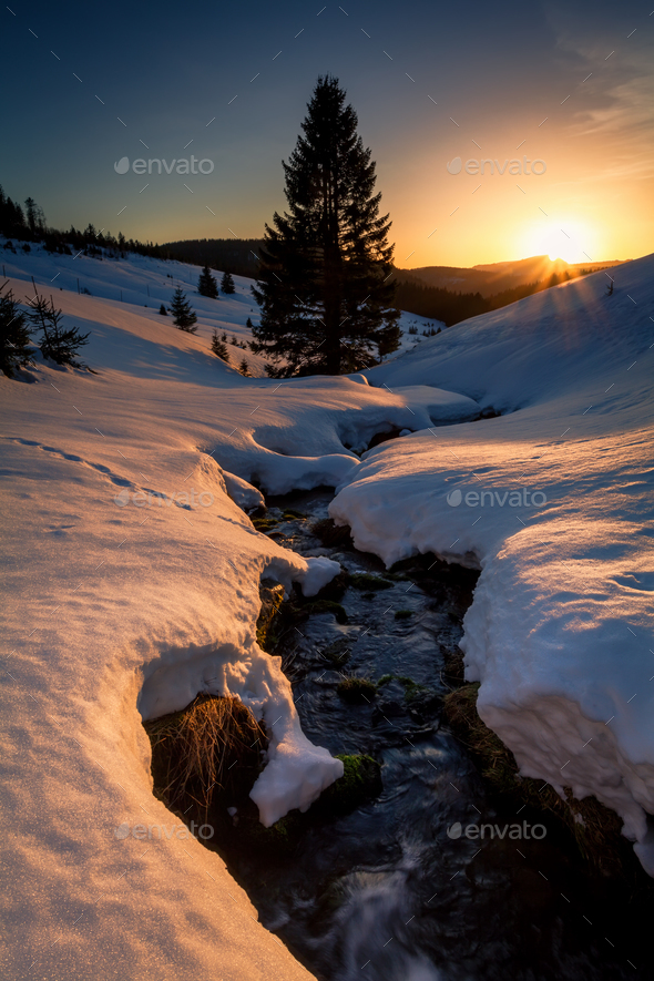 last sunrays over mountains river in winter - Stock Photo - Images