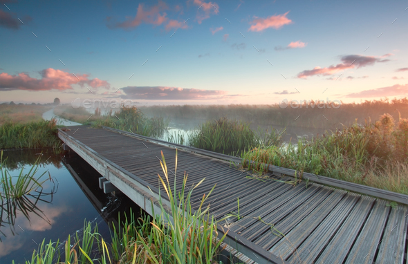wooden biking bridge over river at sunrise - Stock Photo - Images