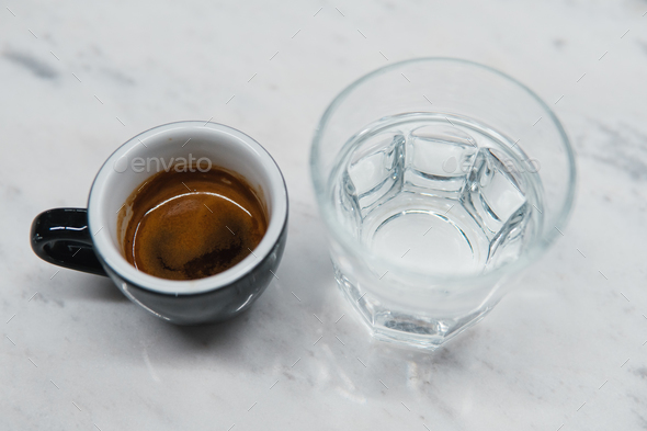 cup with coffee near a glass of water - Stock Photo - Images