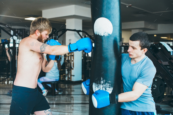 Boxer with punching bag in gym - Stock Photo - Images