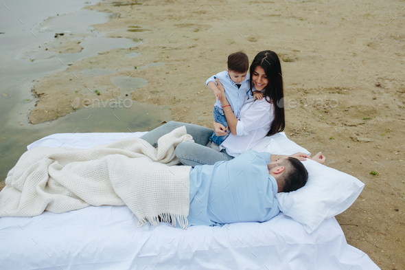 Happy young family relaxing together on the lake - Stock Photo - Images