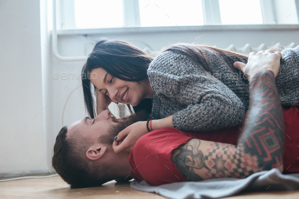 man and woman lying on the floor - Stock Photo - Images