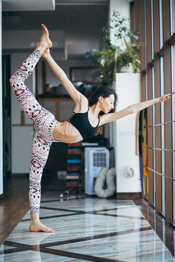 Young attractive woman practicing yoga near window - Stock Photo - Images