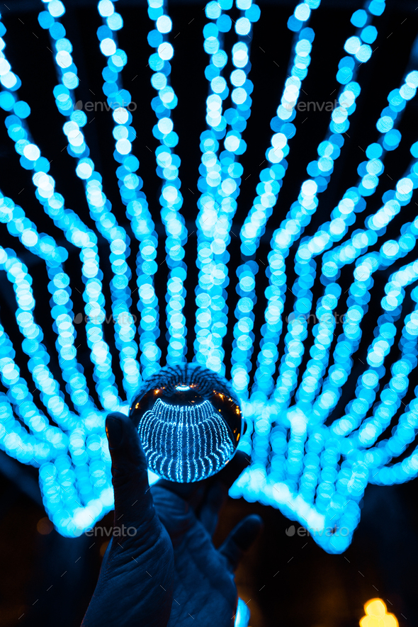 crystal ball stay in blue garland lights - Stock Photo - Images