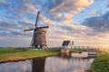 Windmill near the water canal at sunrise in Netherlands