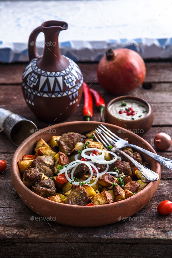 Big ceramic plate with roasted meat and potatoes with onion and wine. - Stock Photo - Images