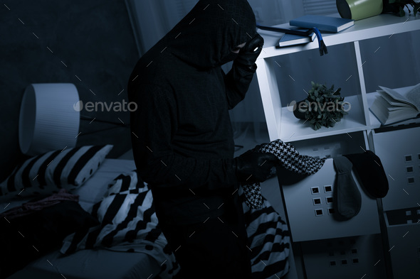 Robber in dark messy room - Stock Photo - Images