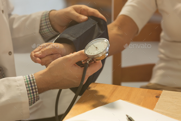 Doctor checking patient's blood pressure - Stock Photo - Images