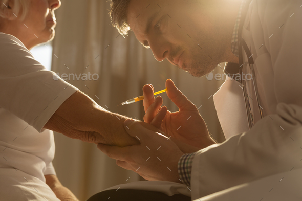 Doctor doing an injection - Stock Photo - Images