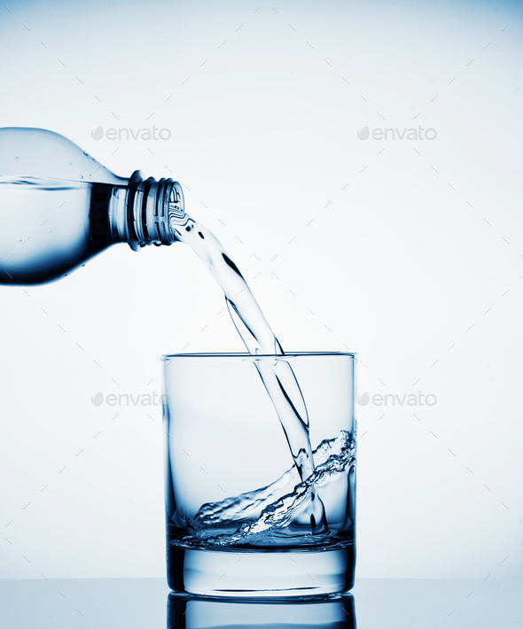 water pouring into a wide glass from a bottle stock photo by alexlukin