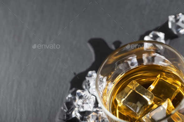 Fragment of glass of whiskey with ice on black background - Stock Photo - Images