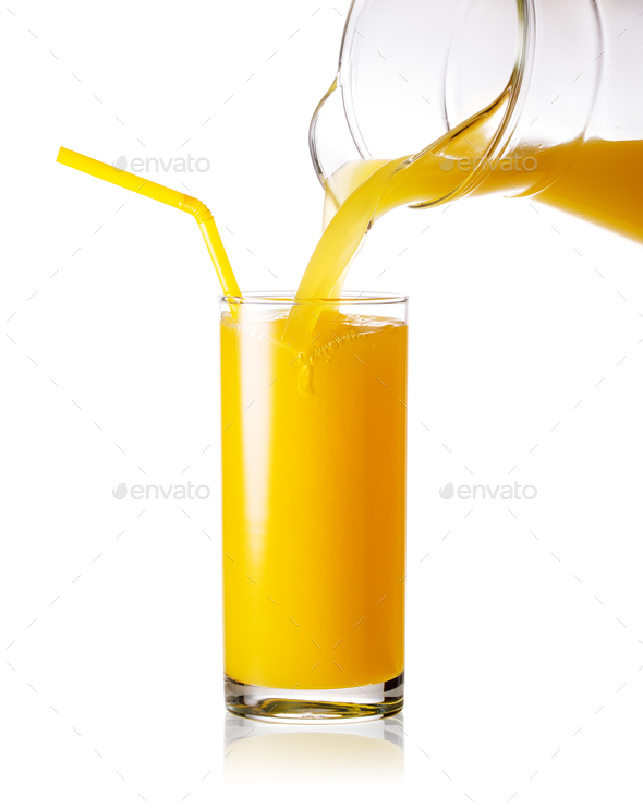 Orange juice pouring from jug into a glass with straw - Stock Photo - Images