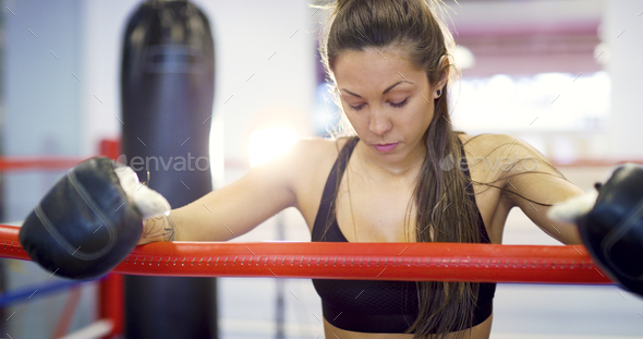 Young female boxer resting with her arms on the ring ropes - Stock Photo - Images