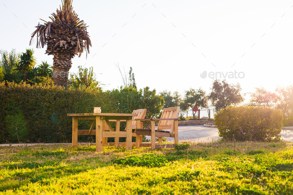 Wooden outdoor furniture. Lounge chairs in hotel garden invite you to relax