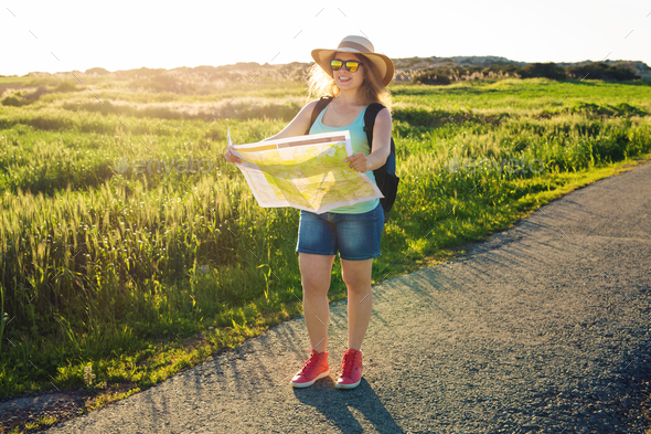woman traveler with backpack checks map to find directions - Stock Photo - Images