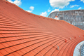 Tile roof with blue sky and clouds in background