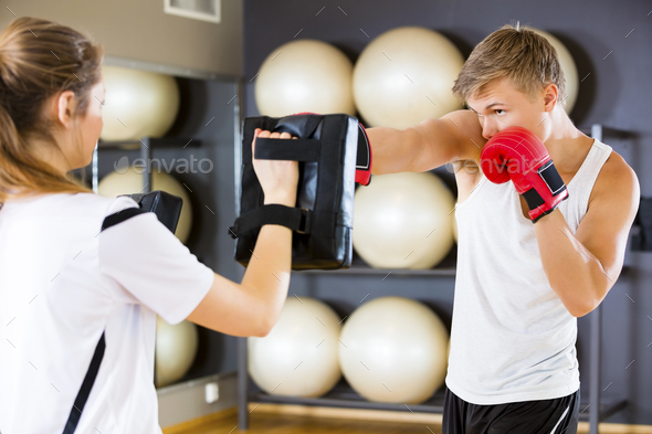 Dedicated Boxer Punching Bag Held By Instructor - Stock Photo - Images