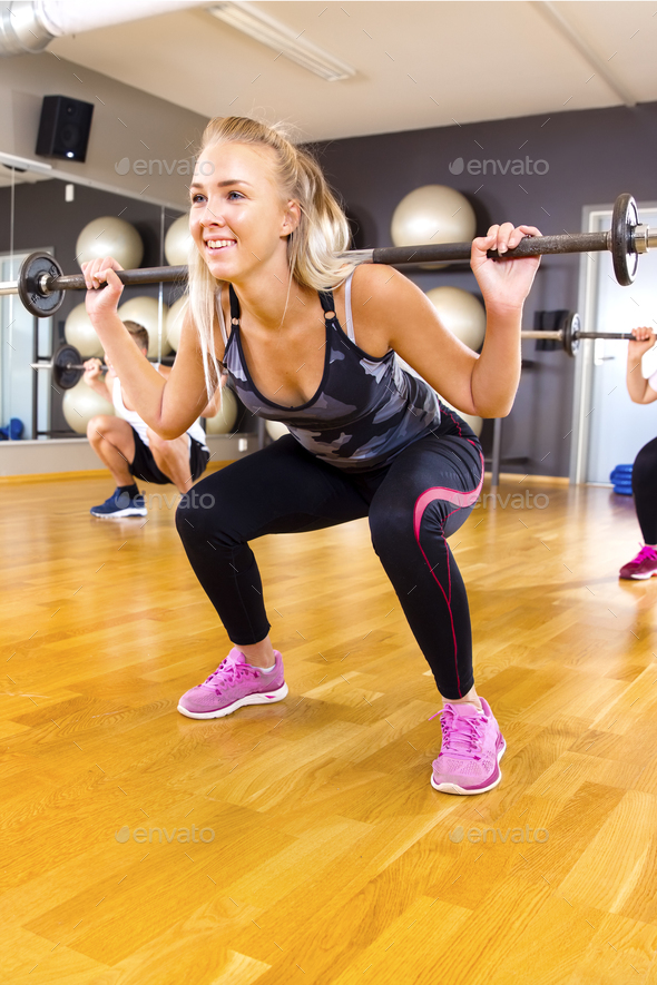 Smiling young woman training squat exercises in group at fitness gym - Stock Photo - Images