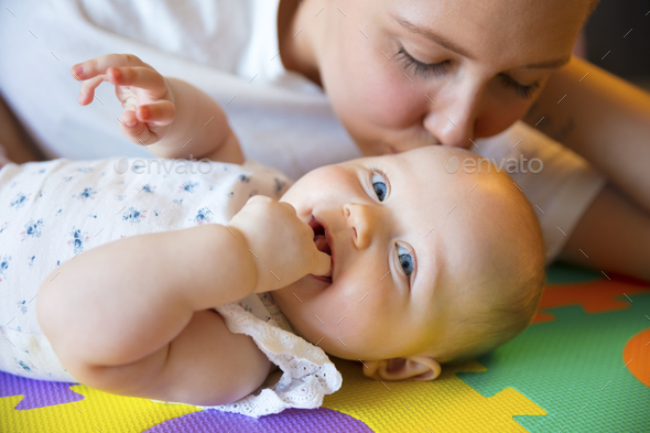 Caring mother kissing her smiling and cute baby girl - Stock Photo - Images