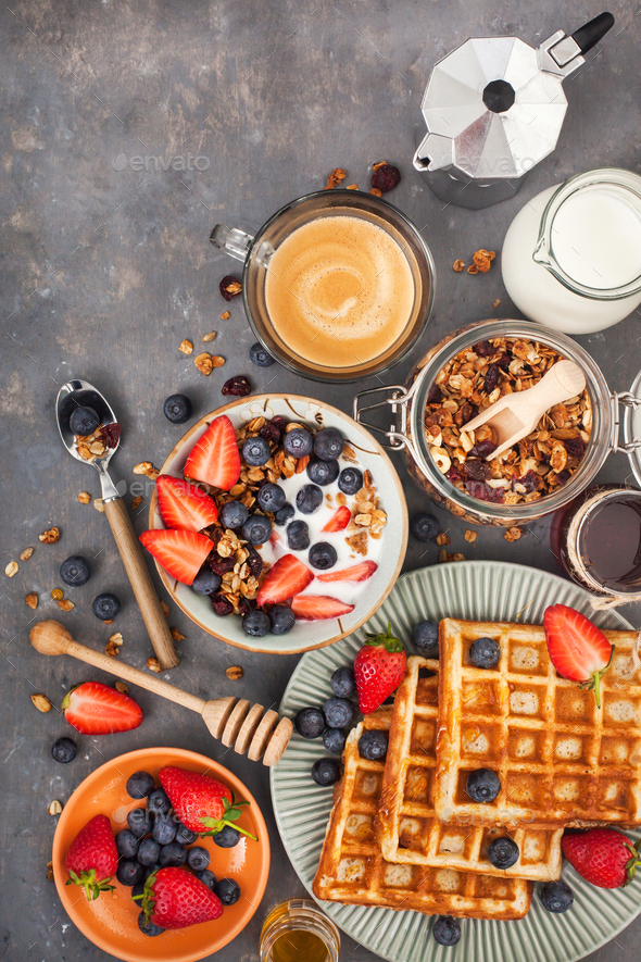 Breakfast table with granola, waffles, berries and coffee - Stock Photo - Images