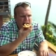 Man Sits in a Cafe at a Table on an Open Terrace and Eats Pizza with His Hands - VideoHive Item for Sale