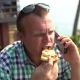 Man Sits in a Cafe at a Table and Eats Pizza and Talking on the Phone - VideoHive Item for Sale