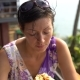 Woman Sits in a Cafe at a Table on a Terrace and Eats Pizza with Her Hands - VideoHive Item for Sale