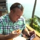 Man Sits in a Restaurant at a Table and Eats Pizza and Using on the Phone - VideoHive Item for Sale