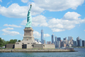 Statue of Liberty island and New York city skyline in a sunny da