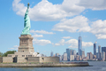 Statue of Liberty island and New York city skyline in sunlight,