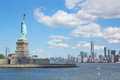 Statue of Liberty and New York city skyline in a sunny day, blue