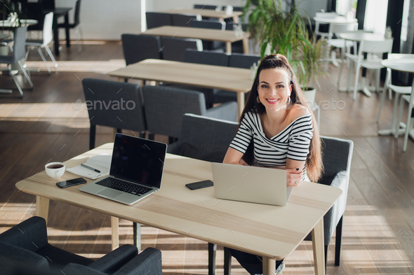 Portrait of a smiling female student writing notes by laptop at cafeteria table. - Stock Photo - Images