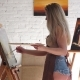 Woman Artist Standing Near Easel Painting on Canvas with Oil