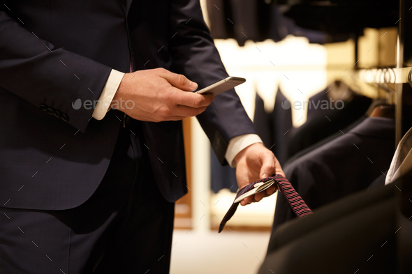 Cropped image of man making photo of price-list - Stock Photo - Images