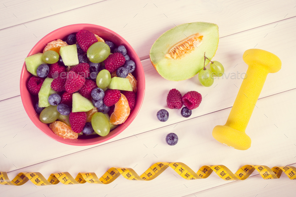 Vintage photo, Fresh fruit salad and centimeter with dumbbells - Stock Photo - Images