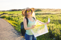 woman traveler with backpack checks map to find directions - PhotoDune Item for Sale