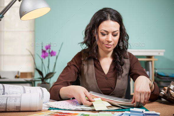 Architect in office picking colors from cards on her desk - Stock Photo - Images