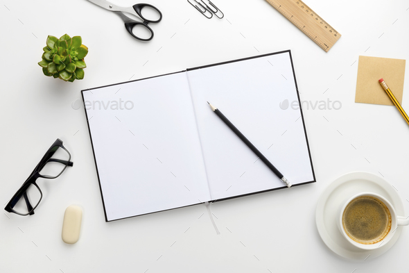 Top view of white office desk with notebook and supplies - Stock Photo - Images