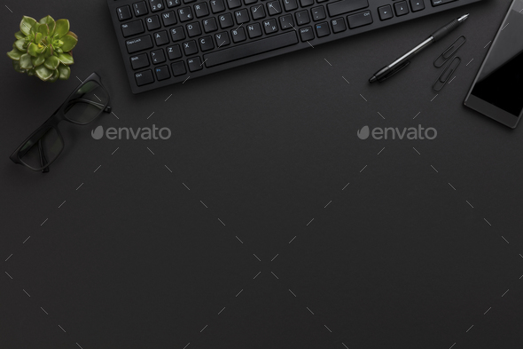 Top view of black office desk with computer and supplies - Stock Photo - Images